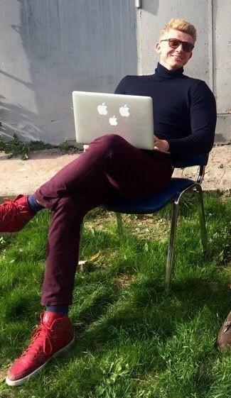 Alexander Zaytsev trägt dunkelblauer Rollkragenpullover, dunkelrote Jeans, rote hohe Sneakers aus Leder, dunkelblaue Socke