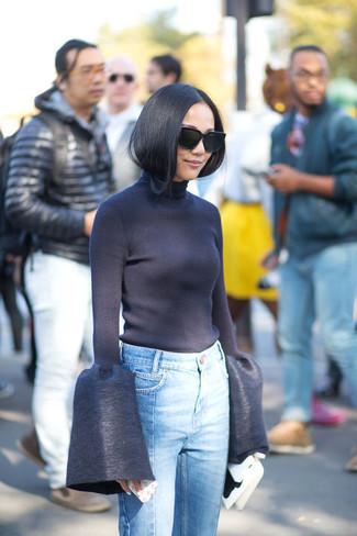 dunkelblauer Rollkragenpullover, hellblaue Jeans, weiße Leder Clutch, schwarze Sonnenbrille für Damen