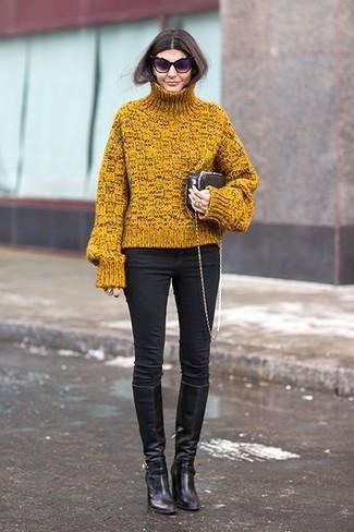 Wie kombinieren: senf Strick Rollkragenpullover, blaue enge Jeans, schwarze kniehohe Stiefel aus Leder, schwarze Leder Clutch