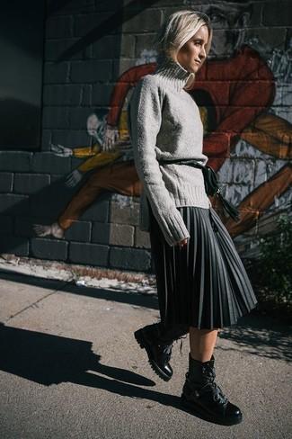 Wie kombinieren: grauer Wollrollkragenpullover, dunkelgrauer Midirock mit Falten, schwarze flache Stiefel mit einer Schnürung aus Leder, dunkelgrüne Leder Bauchtasche