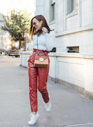 Wie kombinieren: hellblauer Rollkragenpullover, rote Karottenhose aus Leder, weiße Leder niedrige Sneakers, rotbraune Leder Umhängetasche