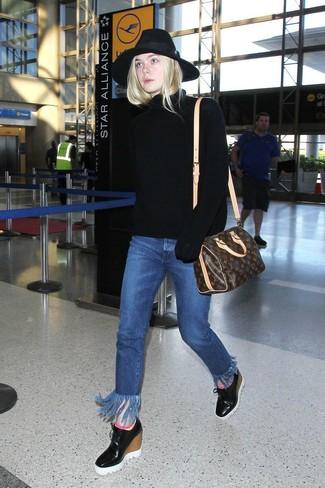 Wie kombinieren: schwarzer Strick Rollkragenpullover, blaue Fransen Jeans, schwarze Keilstiefeletten aus Leder, dunkelbraune bedruckte Leder Reisetasche