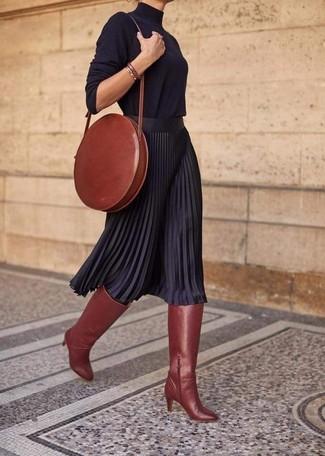 Wie kombinieren: schwarzer Rollkragenpullover, schwarzer Falten Midirock, rotbraune kniehohe Stiefel aus Leder, rotbraune Leder Umhängetasche