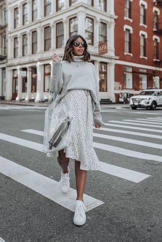 Wie kombinieren: grauer Strick Rollkragenpullover, weißer und schwarzer gepunkteter Midirock, weiße Leder niedrige Sneakers, transparente Gummi Shopper Tasche