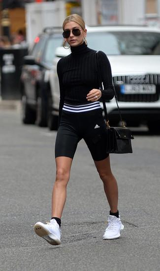 Wie kombinieren: schwarzer Rollkragenpullover, schwarze und weiße Radlerhose, weiße Sportschuhe, schwarze Leder Umhängetasche