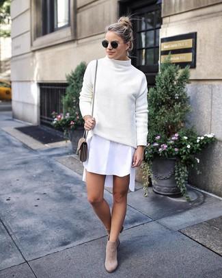 Wie kombinieren: weißer Strick Rollkragenpullover, weißes Shirtkleid, hellbeige Wildleder Stiefeletten, hellbeige Wildleder Umhängetasche