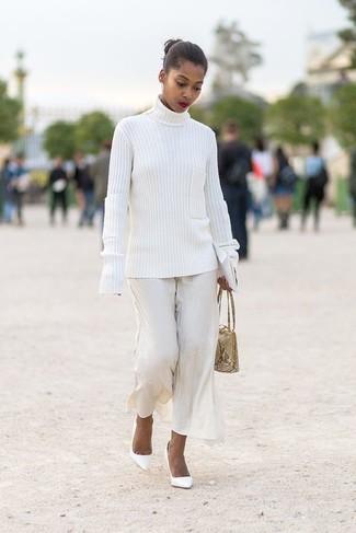 Wie kombinieren: weißer Strick Rollkragenpullover, weiße weite Hose, weiße Leder Pumps, hellbeige Lederhandtasche mit Schlangenmuster