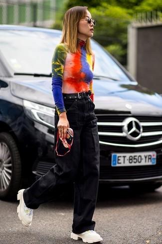 Wie kombinieren: mehrfarbiger Mit Batikmuster Rollkragenpullover, schwarze weite Hose aus Jeans, hellbeige Sportschuhe, schwarzer Ledergürtel