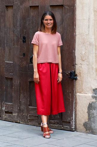 Wie kombinieren: rosa T-Shirt mit einem Rundhalsausschnitt, roter Hosenrock, braune Leder Sandaletten
