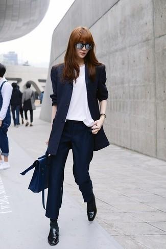 Wie kombinieren: dunkelblaues vertikal gestreiftes Sakko, weißes ärmelloses Oberteil aus Seide, dunkelblaue vertikal gestreifte Anzughose, schwarze Leder Slipper