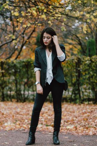 Wie kombinieren: schwarzes vertikal gestreiftes Sakko, weißes ärmelloses Oberteil mit Rüschen, schwarze enge Jeans, schwarze Leder Stiefeletten