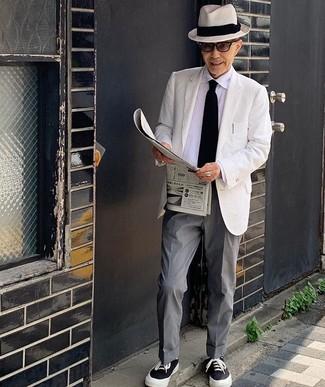 Mode für Herren ab 60: Tragen Sie ein weißes Sakko und eine graue Anzughose für einen stilvollen, eleganten Look. Schwarze und weiße Segeltuch niedrige Sneakers verleihen einem klassischen Look eine neue Dimension.