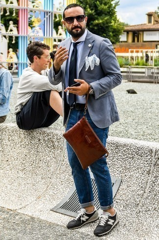 Graues Sakko kombinieren: trends 2020: Kombinieren Sie ein graues Sakko mit blauen Jeans für Drinks nach der Arbeit. Warum kombinieren Sie Ihr Outfit für einen legereren Auftritt nicht mal mit schwarzen und weißen Wildleder niedrigen Sneakers?