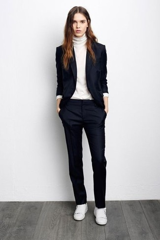 dunkelblaues Sakko, weißer Rollkragenpullover, dunkelblaue Anzughose, weiße niedrige Sneakers für Damen