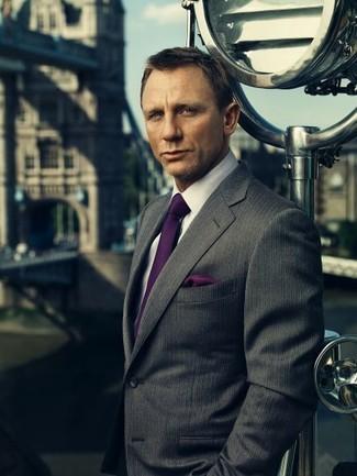 Daniel Craig trägt dunkelgraues vertikal gestreiftes Sakko, weißes Businesshemd, dunkellila Seidekrawatte, dunkellila Seide Einstecktuch