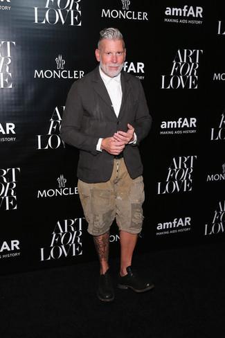 Nick Wooster trägt dunkelgraues Leinen Sakko, weißes Businesshemd, beige Shorts, schwarze Leder Oxford Schuhe