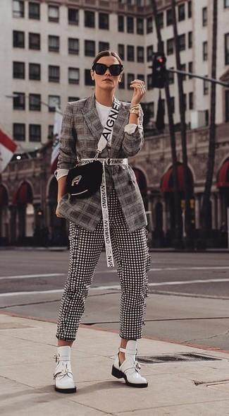 Wie kombinieren: dunkelbraunes Sakko mit Schottenmuster, schwarze und weiße enge Hose mit Vichy-Muster, weiße Leder Stiefeletten mit Ausschnitten, schwarze Wildleder Umhängetasche