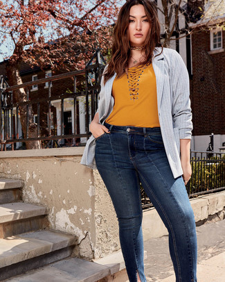 Wie kombinieren: graues vertikal gestreiftes Sakko, senf T-Shirt mit einem V-Ausschnitt, dunkelblaue enge Jeans, goldene enge Halskette