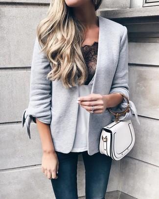 Wie kombinieren: graues Strick Sakko, weißes und schwarzes Spitze Trägershirt, dunkelblaue enge Jeans, weiße Lederhandtasche