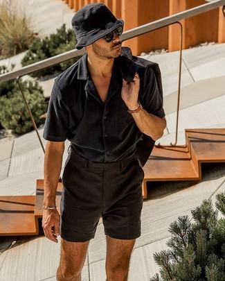 Wie kombinieren: schwarzes Leinen Sakko, schwarzes Kurzarmhemd, schwarze Leinen Shorts, schwarzer Fischerhut