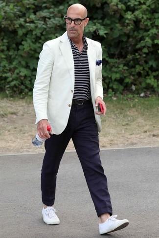 Stanley Tucci trägt weißes Sakko, dunkelblaues und weißes horizontal gestreiftes Polohemd, dunkelblaue Chinohose, weiße Segeltuch niedrige Sneakers