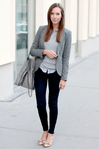 graues Sakko, grauer Pullover mit einem Rundhalsausschnitt, graues Businesshemd, dunkelblaue enge Jeans für Damen