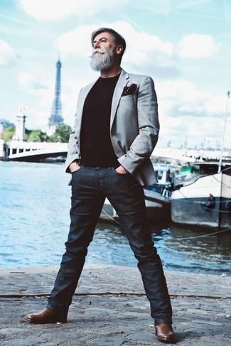 Wie kombinieren: graues Sakko, schwarzer Pullover mit einem Rundhalsausschnitt, dunkelblaue Jeans, braune Chelsea-Stiefel aus Leder