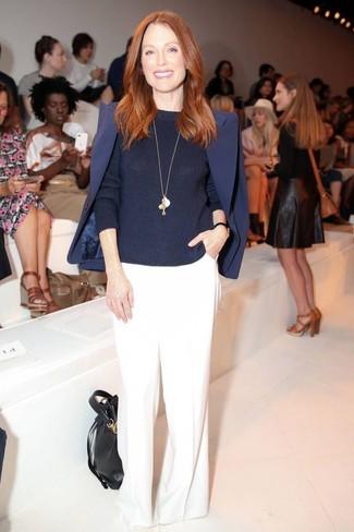 Julianne Moore trägt dunkelblaues Sakko, dunkelblauer Pullover mit einem Rundhalsausschnitt, weiße weite Hose, schwarze Leder Beuteltasche