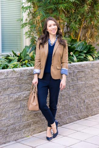 beige Sakko, dunkelblauer Pullover mit einem V-Ausschnitt, blaues Jeanshemd, dunkelblaue Anzughose für Damen