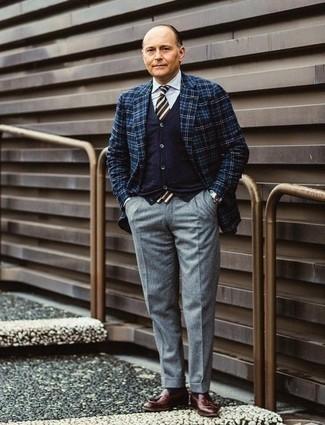 Dunkelblaue Strickjacke kombinieren: trends 2020: Kombinieren Sie eine dunkelblaue Strickjacke mit einer grauen Wollanzughose für einen stilvollen, eleganten Look. Ergänzen Sie Ihr Look mit dunkelroten Leder Slippern mit Quasten.