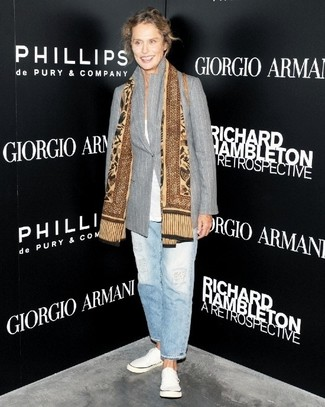 Lauren Hutton trägt graues vertikal gestreiftes Sakko, weißes T-Shirt mit einem Rundhalsausschnitt, hellblaue Boyfriend Jeans, weiße Leinenschuhe