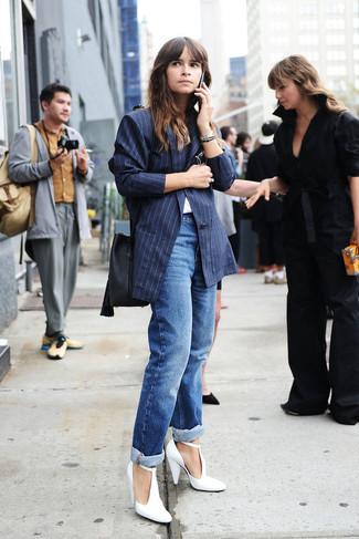 Miroslava Duma trägt dunkelblaues vertikal gestreiftes Sakko, weißes T-Shirt mit einem Rundhalsausschnitt, blaue Boyfriend Jeans, weiße Leder Pumps