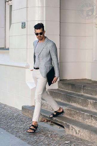 Herren Outfits & Modetrends 2020: Kombinieren Sie ein graues Sakko mit einer weißen Chinohose, um einen eleganten, aber nicht zu festlichen Look zu kreieren. Schwarze Ledersandalen liefern einen wunderschönen Kontrast zu dem Rest des Looks.