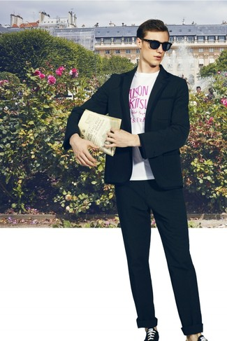 Wie kombinieren: schwarzes Sakko, weißes und rosa bedrucktes T-Shirt mit einem Rundhalsausschnitt, schwarze Chinohose, schwarze und weiße Segeltuch niedrige Sneakers