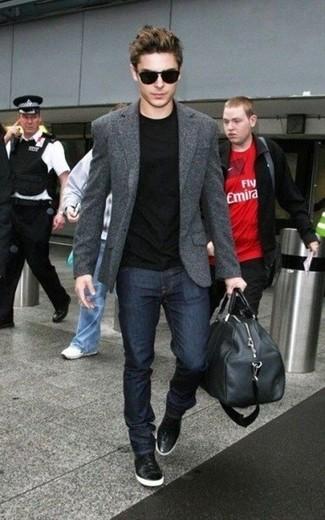 Zac Efron trägt dunkelgraues Wollsakko, schwarzes T-Shirt mit einem Rundhalsausschnitt, dunkelblaue Jeans, schwarze hohe Sneakers aus Leder