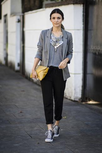 Wie kombinieren: graues Sakko, graues T-Shirt mit einem Rundhalsausschnitt, schwarze Karottenhose, schwarze und weiße Segeltuch niedrige Sneakers