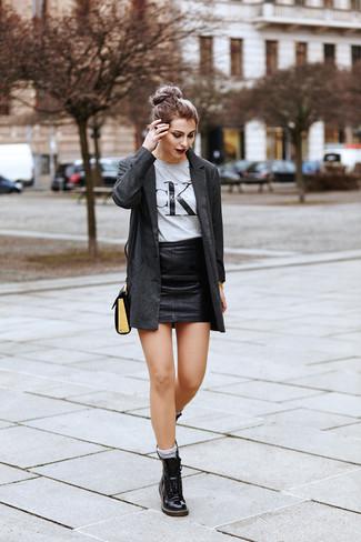 Wie kombinieren: dunkelgraues Sakko, graues bedrucktes T-Shirt mit einem Rundhalsausschnitt, schwarzer Leder Minirock, schwarze flache Stiefel mit einer Schnürung aus Leder