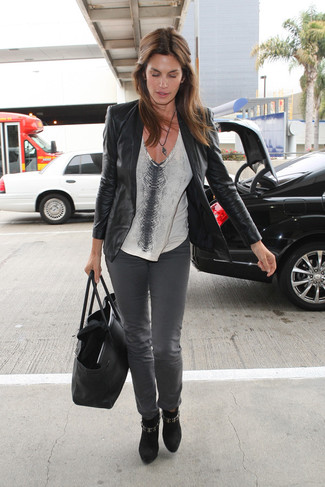 Wie kombinieren: schwarzes Ledersakko, graues T-Shirt mit einem V-Ausschnitt mit Schlangenmuster, graue Jeans, schwarze Wildleder Stiefeletten