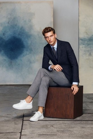 Weiße Leder niedrige Sneakers kombinieren für Herbst: trends 2020: Kombinieren Sie ein dunkelblaues Sakko mit einer grauen Chinohose, wenn Sie einen gepflegten und stylischen Look wollen. Weiße Leder niedrige Sneakers verleihen einem klassischen Look eine neue Dimension. Der Look ist mega für den Herbst.