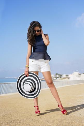 Wie kombinieren: dunkelblaues Schößchen-Top, weiße Shorts, rote Keilsandaletten aus Wildleder, weißer und schwarzer Strohhut