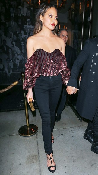 Wie kombinieren: dunkelrotes schulterfreies Oberteil aus Samt, schwarze enge Jeans, schwarze Wildleder Sandaletten, schwarze und goldene Clutch