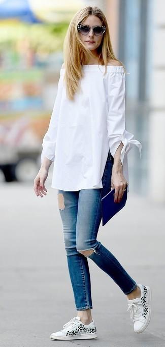 Olivia Palermo trägt Weißes Schulterfreies Oberteil, Blaue Enge Jeans mit Destroyed-Effekten, Weiße Niedrige Sneakers mit Blumenmuster, Blaue Leder Clutch