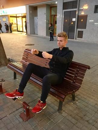 Alexander Zaytsev trägt schwarze Bomberjacke, schwarze Chinohose, rote Sportschuhe