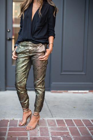 Wie kombinieren: schwarze Langarmbluse, goldene enge Hose, silberne Leder Sandaletten