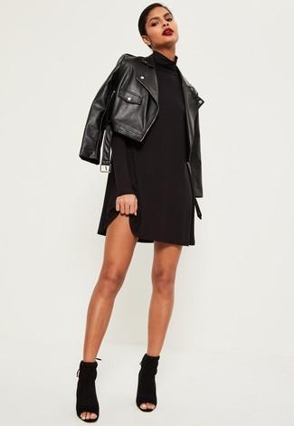 Wie kombinieren: schwarze Leder Bikerjacke, schwarzes schwingendes Kleid, schwarze Wildleder Stiefeletten mit Ausschnitten