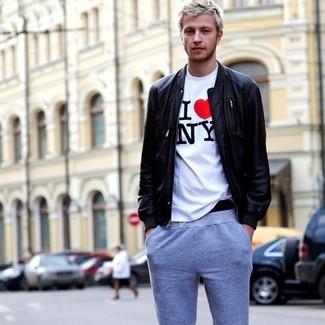 Wie kombinieren: schwarze Leder Bomberjacke, weißes bedrucktes T-Shirt mit einem Rundhalsausschnitt, graue Jogginghose
