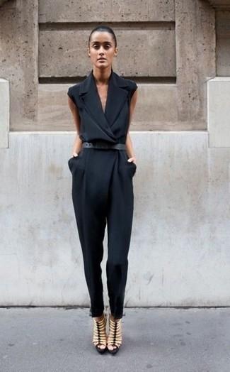 Wie kombinieren: schwarzer Jumpsuit, hellbeige Römersandalen aus Leder, schwarzer Ledergürtel