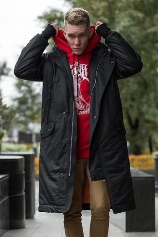 Wie kombinieren: schwarzer Parka, roter und weißer bedruckter Pullover mit einem Kapuze, beige Chinohose