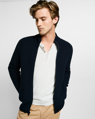 Wie kombinieren: schwarzer Pullover mit einem Reißverschluß, weißes T-shirt mit einer Knopfleiste, beige Chinohose