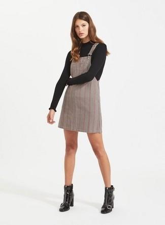 Wie kombinieren: schwarzer Pullover mit einem Rundhalsausschnitt, grauer Kleiderrock mit Schottenmuster, schwarze Leder Stiefeletten